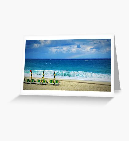 Deck chairs on beach with faraway rainbow Greeting Card