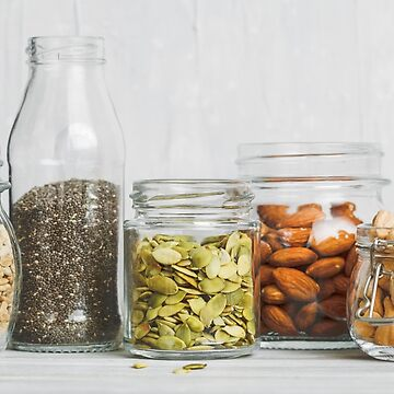 Various nuts and seeds in glass jars over white wooden table against white background.  by Edalin
