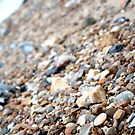 Stones and pebbles on a beach by cocodesigns