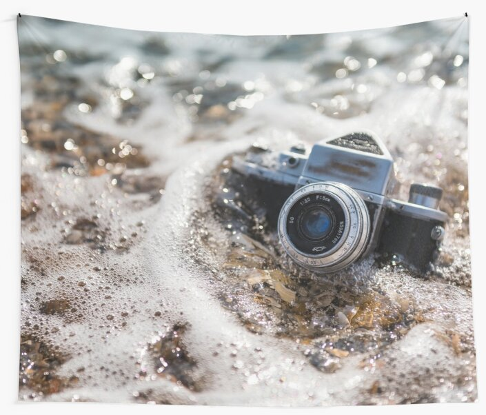 Retro photo camera in the water on the beach, sinks in sea foam by lenaivanova
