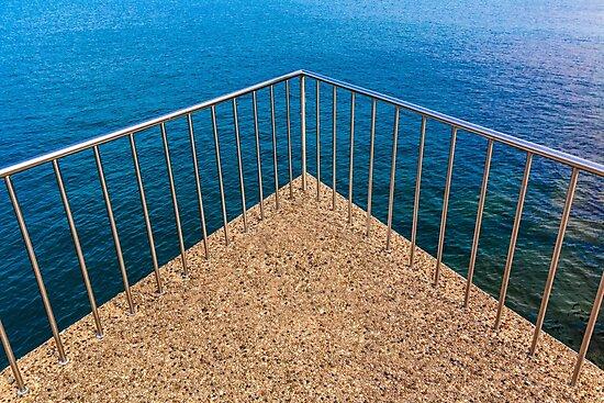 Geometric triangular balcony railings over deep blue lake water by Chris Warham