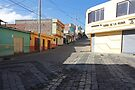Guamote, Ecuador colourful buildings on steep cobblestone street by Kendall Anderson