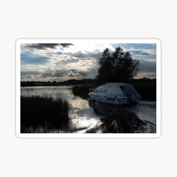 A boat travelling the Norfolk Broads near dusk Sticker