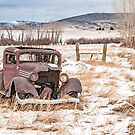 Rusty Antique Vehicle in a Field Covered with Snow by Sue Smith