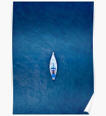 A drone shot of a sailing boat surrounded by deep blue sea water Poster