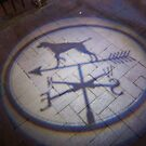 Illuminated weather Vane image cast onto the sidewalk in Houston, Texas by David Carton