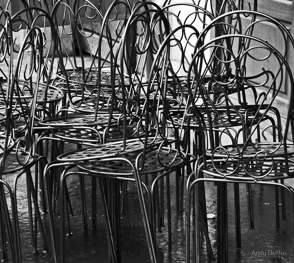 Stacked cafe chairs, washed streets, Sunday morning......Paris by Andy Duffus