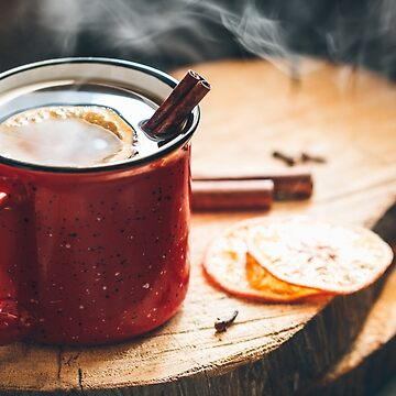 Mulled wine in a red ceramic mug over rustic wooden boards surrounded spices. by Edalin