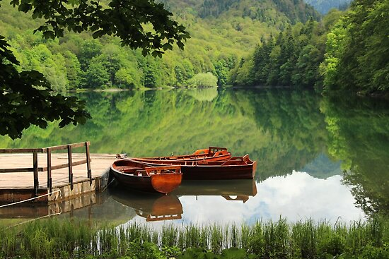 Fresh water lake with wooden boats by Vanka