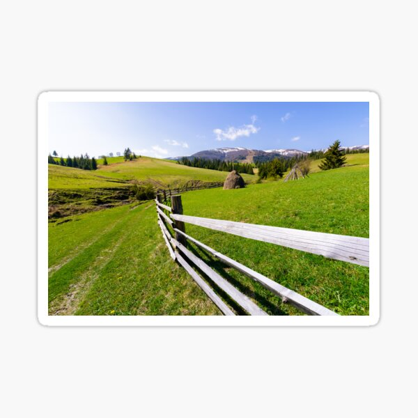 haystack behind the wooden fence on a grassy hill Sticker
