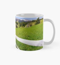 haystack behind the wooden fence on a grassy hill Mug