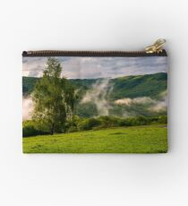 fog rising behind the forest on a hillside Studio Pouch