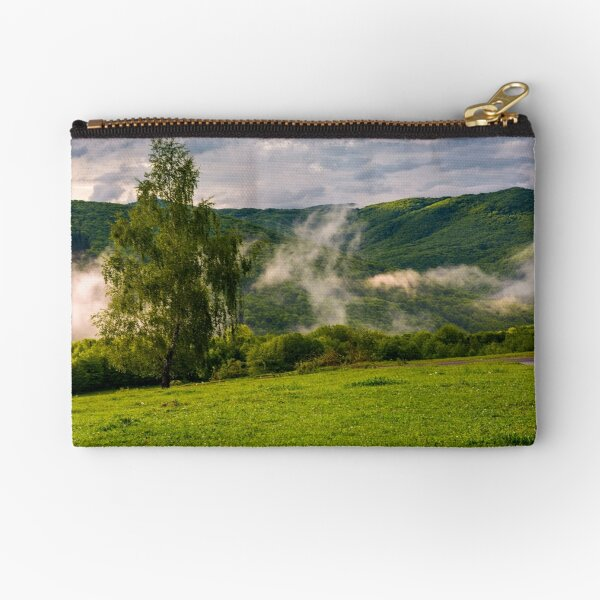fog rising behind the forest on a hillside Zipper Pouch