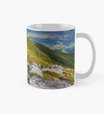 huge rocky formations on the grassy hills Mug