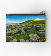 huge rocky formation on the grassy hillside Studio Pouch