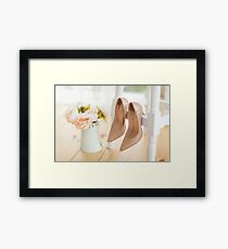 beige shoes for bride hanging on a white chair against a background of a bouquet of pions Framed Print