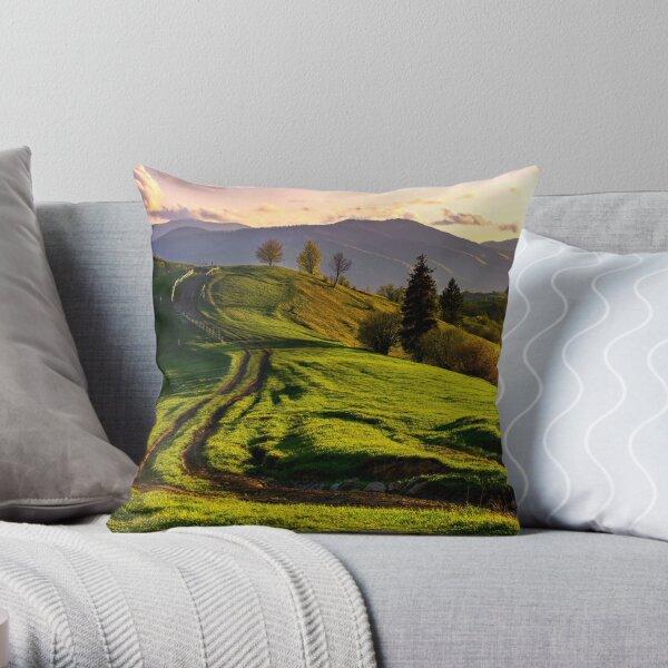 road through green hills at sunset Throw Pillow
