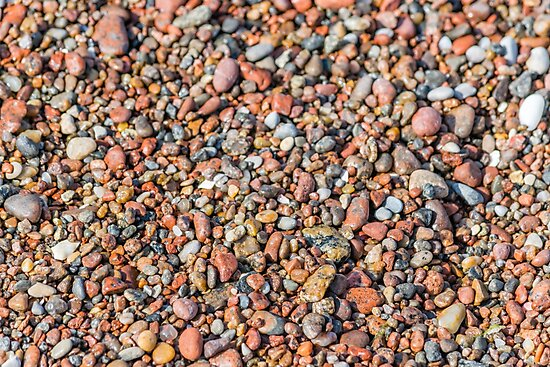 Small Wet Stones on a Beach by Jon Shore