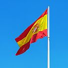 Spanish flag waving against clear blue sky by Lukasz Szczepanski