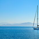 white sailboat in a blue lagoon by patrick pichard