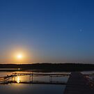 Evening landscape of moon rise over calm lake by Lukasz Szczepanski