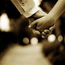 Bride and groom holding hands sepia toned black and white silver gelatin 35mm film analog wedding photograph by edwardolive