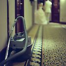 Wedding bride and groom and vacuum cleaner in hotel corridor by edwardolive
