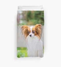 Portrait of a papillon purebreed dog with grass behind Duvet Cover