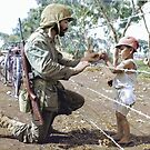 A U.S. Marine reaches through the barbed wire of a civilian containment area to give a young Japanese boy candy during the Battle of Tinian.  by Marina Amaral