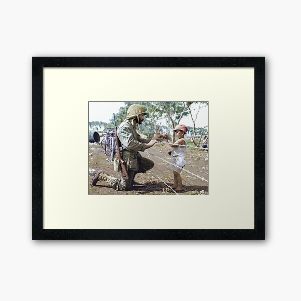A U.S. Marine reaches through the barbed wire of a civilian containment area to give a young Japanese boy candy during the Battle of Tinian.  Framed Art Print