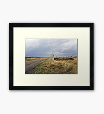 old pilgrim's trail marker beneath stormy clouds Framed Print