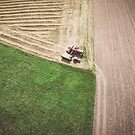 Aerial view of combine-harvester and tractor working in the field by Lukasz Szczepanski