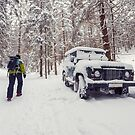 Tourist walking alone through winter forest passing off-road parked car by Lukasz Szczepanski