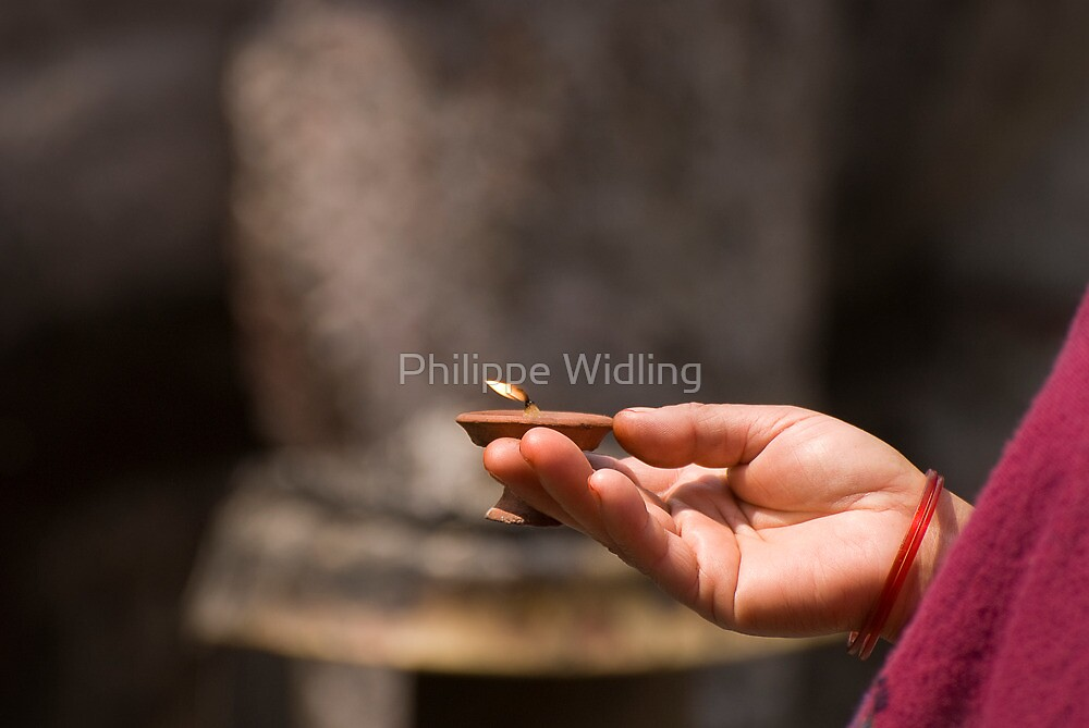 Prayer's hand holding a candle. by Philippe Widling