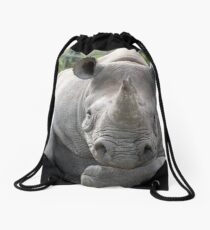 Rhino looking relaxed with head resting on forearm. Drawstring Bag