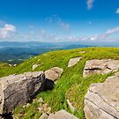huge rocks on the grassy mountain side by mike-pellinni