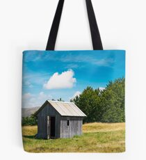 wooden hut on a grassy meadow Tote Bag
