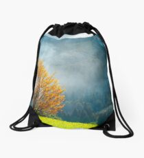 tree with golden foliage on grassy hillside Drawstring Bag