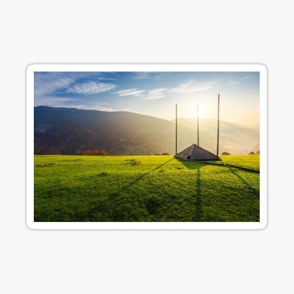 empty hay barrack on a grassy hill at sunrise Sticker