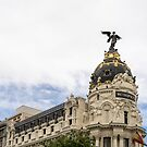 Gallivanting Around Madrid is a Pure Delight - Iconic Metropolis Building with White Clouds by Georgia Mizuleva