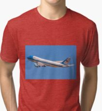 Air force One in flight with a blue sky background  Tri-blend T-Shirt