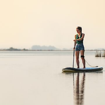 Woman stand up paddleboarding by homydesign
