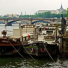 Boats anchored to the riverbank in Paris by retouch