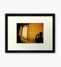 The shadow of a man on the illuminated wall of a house Framed Print