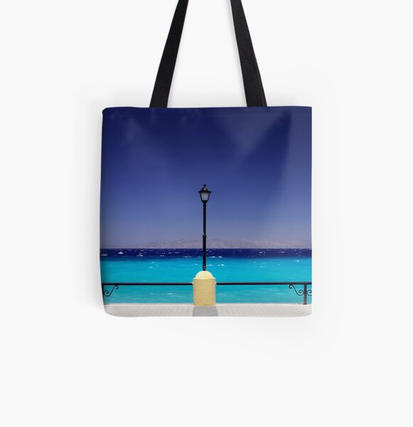 Turquoise sea with dark blue sky and a pylon in Greece All Over Print Tote Bag