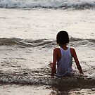 Boy watching the waves roll in by Michael Brewer