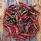 Dried chili peppers on a wooden board by naturalis