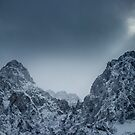 Sunlight and dark clouds over snowy mountains by Patrik Lovrin
