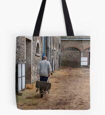 Man pulling a wheelbarrow Tote Bag