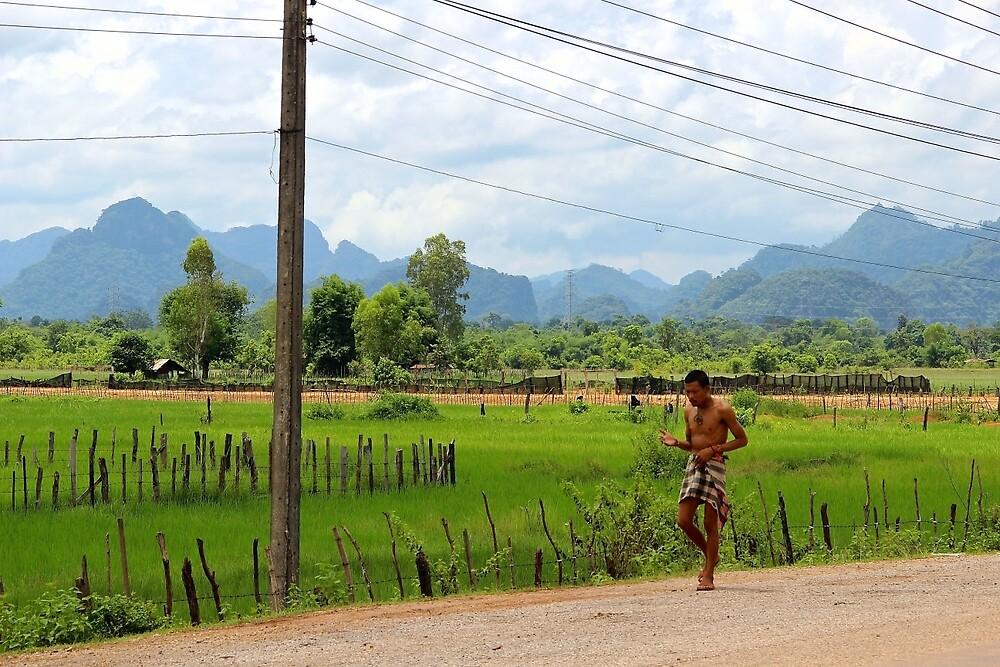 Walking along the Road - Thakhek, Laos. by Tiffany Lenoir